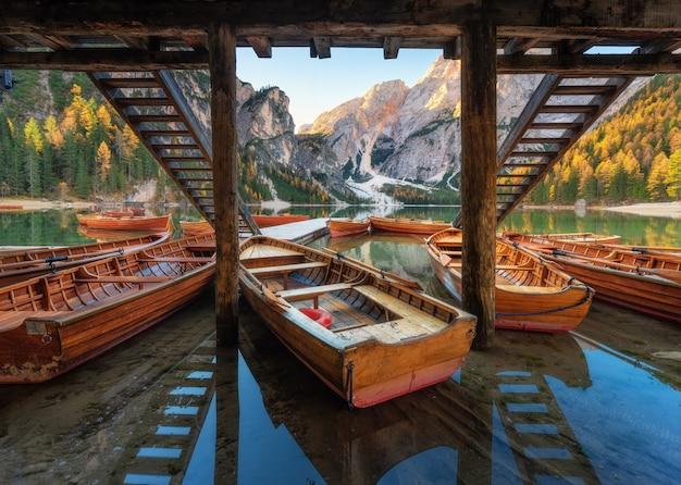 Bateaux en bois près de la maison dans le lac braies au lever du soleil en automne
