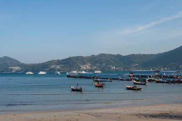 Les bateaux de croisière et les bateaux de pêche se tiennent sur la jetée.