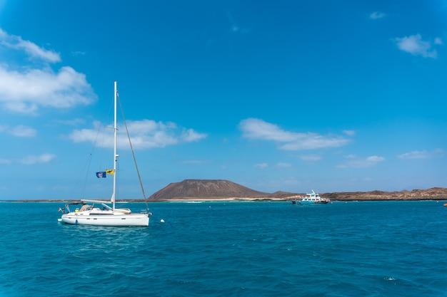 Bateaux dans l'eau turquoise sur isla de lobos, au large de la côte nord de fuerteventura, îles canaries. espagne