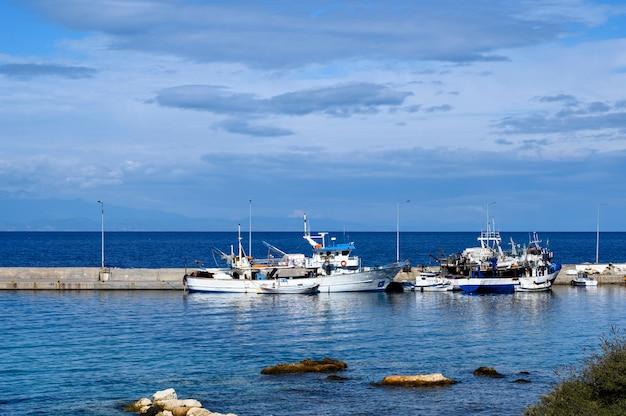 Bateaux dans le port de nea roda sur l'eau de mer bleue, halkidiki, grèce