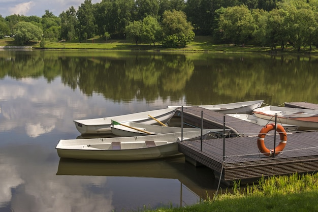 Bateaux à l'embarcadère sur une petite rivière. la bouée de sauvetage est suspendue au quai