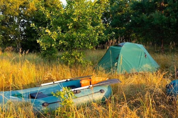 Bateaux gonflables en caoutchouc avec matériel de pêche et tente touristique tôt le matin dans le brouillard sur la rive du fleuve.