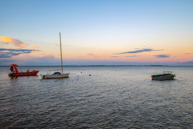 Les bateaux de pêche amarrés à l'embarcadère au bord du rivage au coucher du soleil.