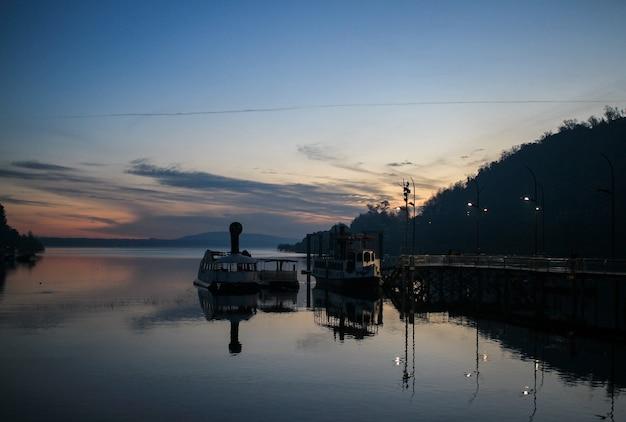 Bateaux de pêche amarrés sur une petite jetée en bois entourée de montagnes pendant le coucher du soleil au chili