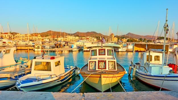 Bateaux de pêche dans le port de la ville d'egine au coucher du soleil, grèce - vue panoramique