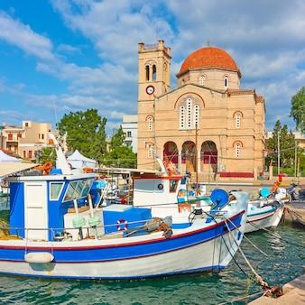 Bateaux de pêche et front de mer avec l'église ekklisia isodia theotokou aux beaux jours d'été dans la ville d'égine, îles saroniques, grèce