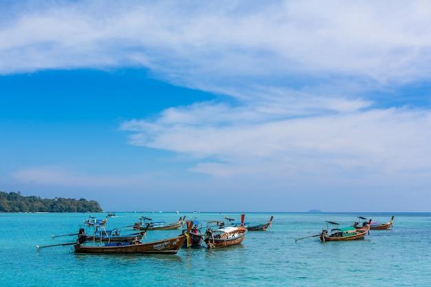 Bateaux de pêche thaïlandais traditionnels enveloppés de rubans colorés.