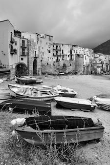 Bateaux sur la plage et vieilles maisons au bord de la mer à cefalu, sicile, italie - paysage noir et blanc