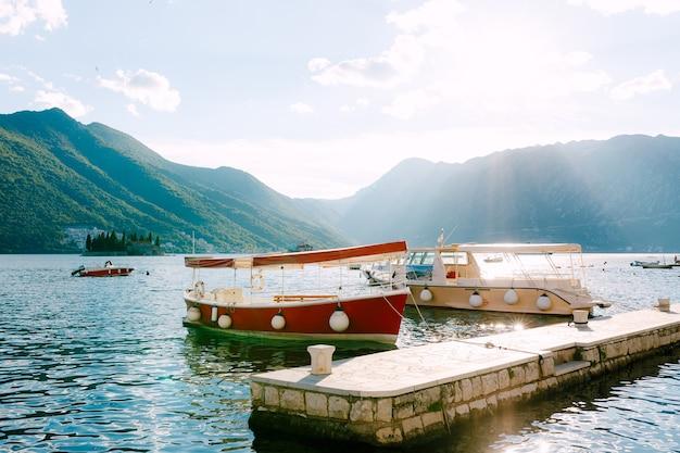 Bateaux de plaisance rouges et beiges sur l'eau à l'embarcadère de la ville de perast