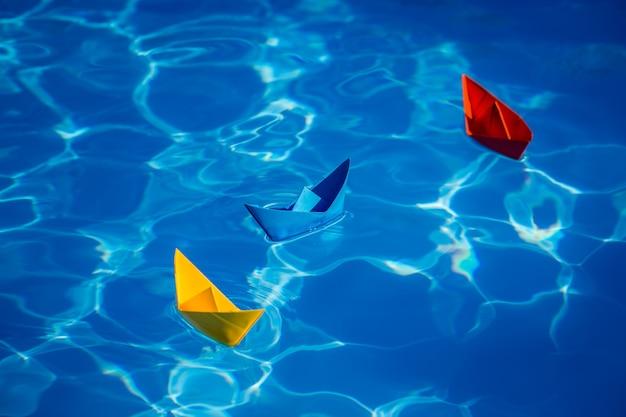Bateaux à voile en papier multicolore sur fond de l'eau bleue