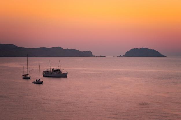 Bateaux voyant le coucher de soleil en août sur la plage de cavalleria, sur la côte nord de minorque, en espagne.