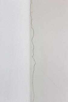 Le bâtiment aux murs blancs s'est fissuré par les intempéries ou l'humidité. fissuré sur la texture du mur blanc.