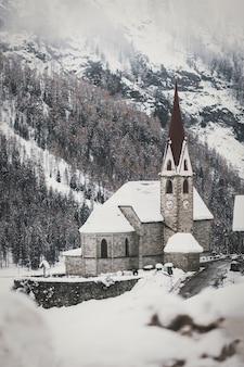 Bâtiment en béton gris couvert de neige à côté des arbres