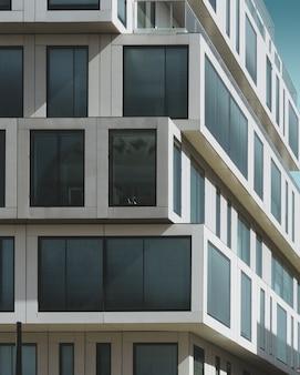 Bâtiment en béton gris avec de grandes fenêtres sous le ciel bleu