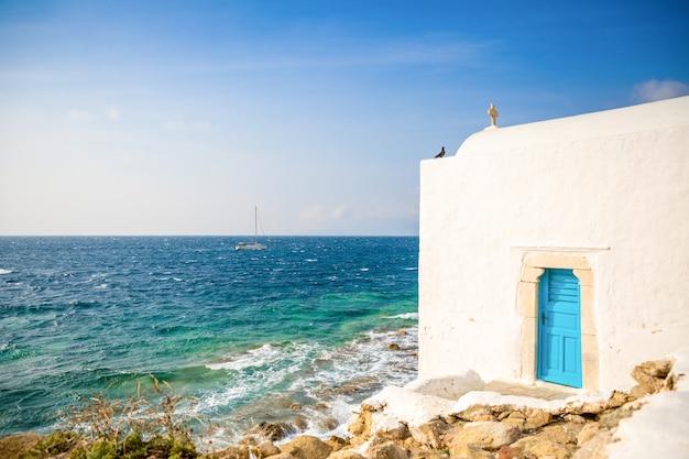 Bâtiment blanc église grecque avec dôme contre le ciel bleu sur l'île de mykonos, grèce