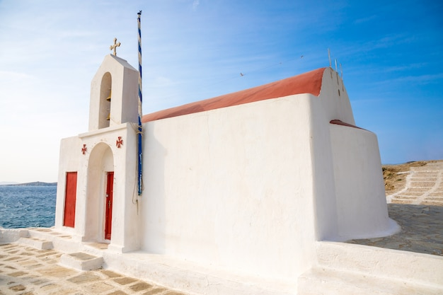 Bâtiment blanc de l'église grecque typique avec un dôme rouge contre le ciel bleu sur l'île de mykonos, grèce