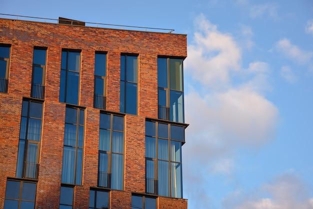 Bâtiment en brique rouge contre le ciel, immeuble de bureaux contre le ciel