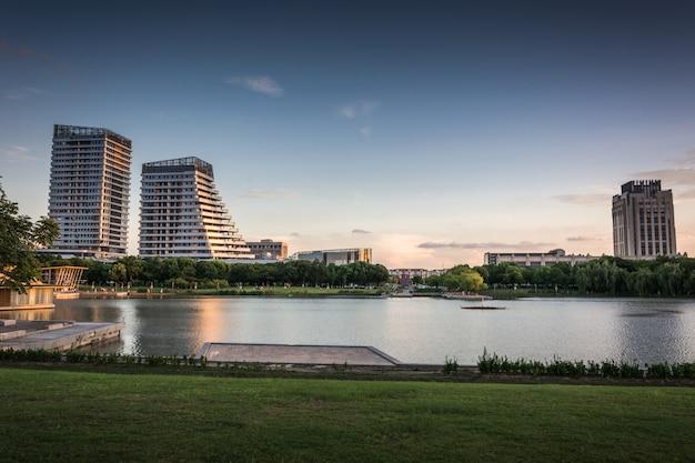 Bâtiment commercial moderne au coucher du soleil au bord du petit lac
