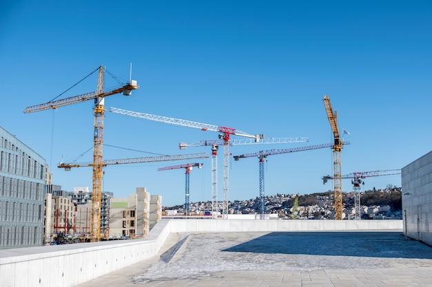 Bâtiment de construction avec des grues et derrick dans la ville