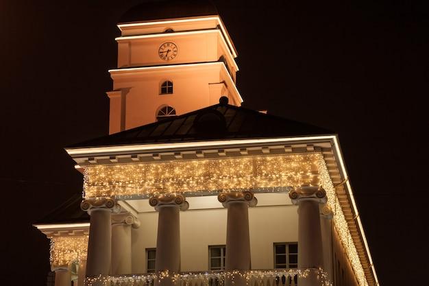Bâtiment européen historique décoré de lumières de noël et de guirlandes