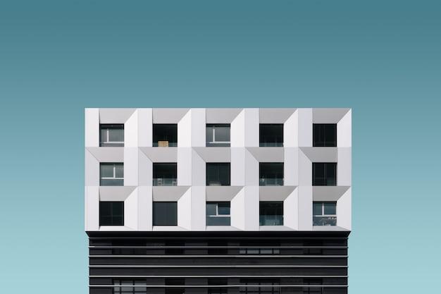 Bâtiment moderne en métal argenté et noir sous le ciel bleu