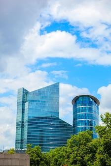 Bâtiment moderne près du parc avec des arbres verts contre le ciel bleu