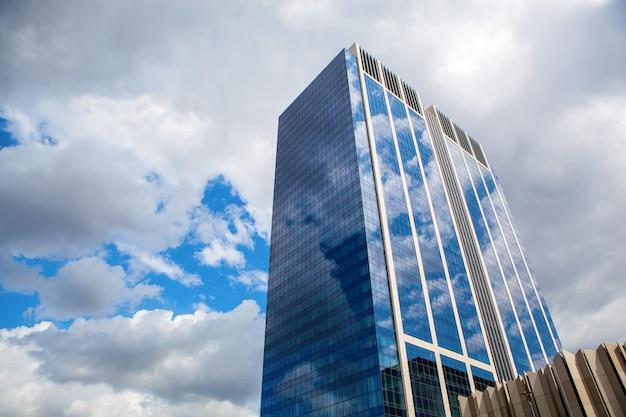 Bâtiment moderne avec reflet du ciel bleu et des nuages
