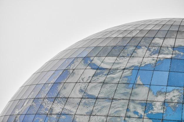 Bâtiment moderne sphérique en verre avec reflet du ciel bleu et des nuages. gros plan, copiez l'espace, isolé.