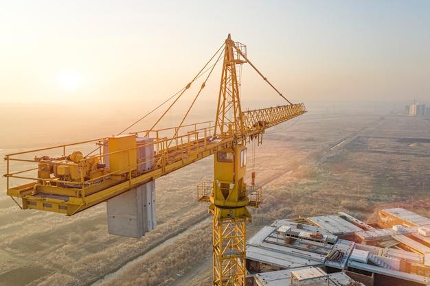 Bâtiment à plusieurs étages, grue à tour et chantier de construction, vue de dessus. au coucher du soleil.