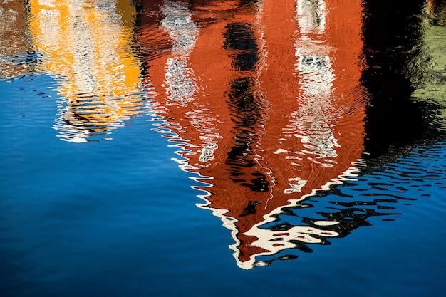 Bâtiment rouge et jaune se reflétant dans le lac