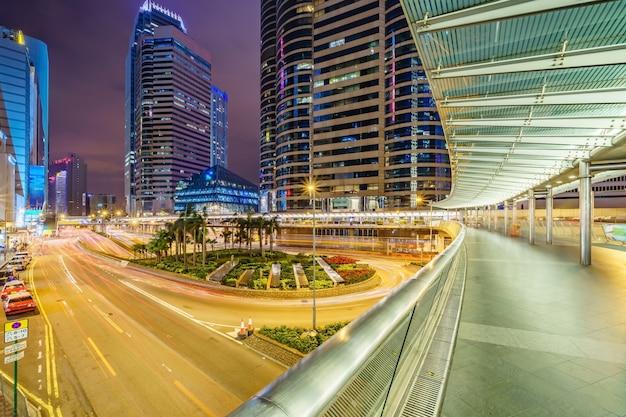 Bâtiments de gratte-ciel de bureau et trafic achalandé sur une route avec des sentiers de lumière de voitures floues.