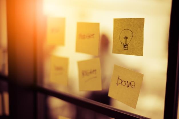 Bâton de bloc-notes de papier jaune sur le concept d'idées de bureau fenêtre d'affaires