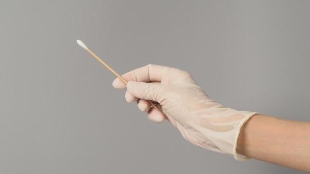 Bâton de coton pour le test d'écouvillon à la main avec des gants médicaux blancs sur fond gris.