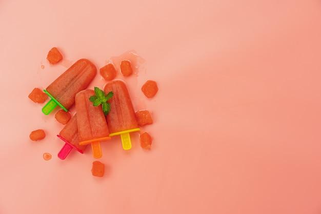 Bâton de crème glacée à la pastèque, posé à plat, fait maison sur un papier peint de papier rose rustique moderne.