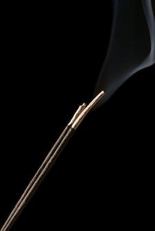 Bâton d'encens isolé sur fond noir