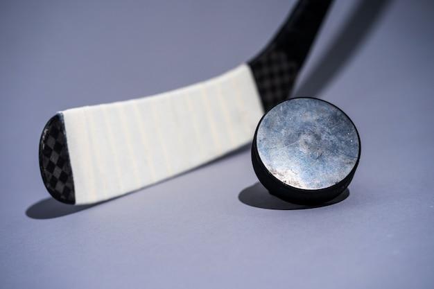 Bâton de hockey sur glace et rondelle sur fond blanc isolé