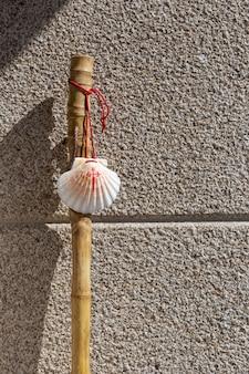 Bâton de marche et coquillage du camino de santiago s'appuyant sur un mur en pierre de granit. concept de pèlerinage de saint jacques de compostelle