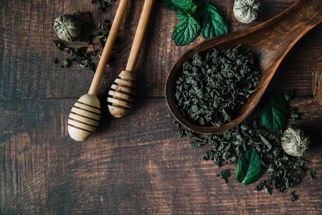 Bâton de miel et une cuillère avec des herbes de thé