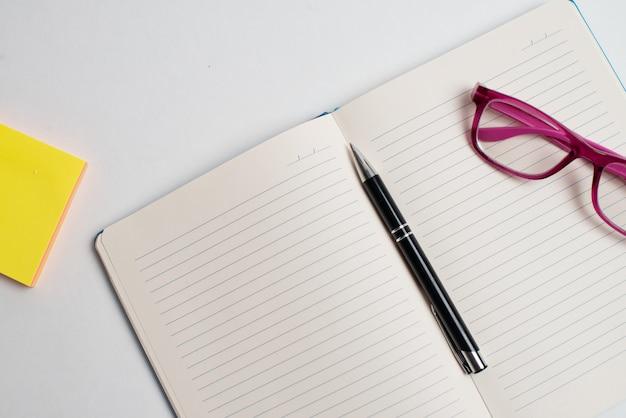 Bâton de note jaune et lunettes et stylo noir