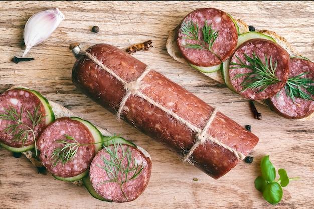 Bâton de saucisse de salami et sandwichs au pain de seigle avec saucisse fumée aneth et concombre sur planche de bois à découper, vue de dessus