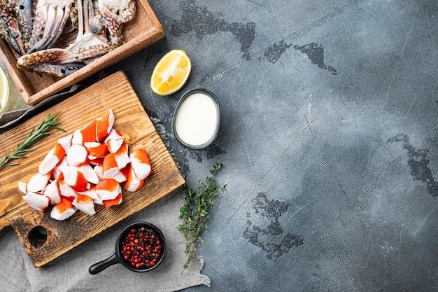 Bâton de viande de crabe frais surimi avec jeu de crabe bleu natation, sur table grise, vue de dessus à plat