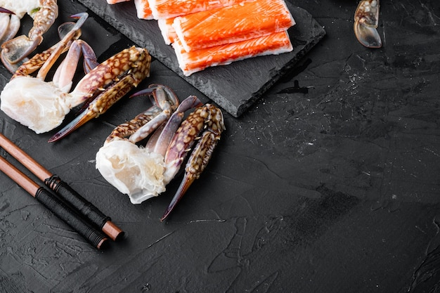 Bâtonnet de chair de crabe frais surimi avec ensemble de crabe bleu nageur, sur fond noir, vue de dessus à plat, avec fond et espace pour le texte