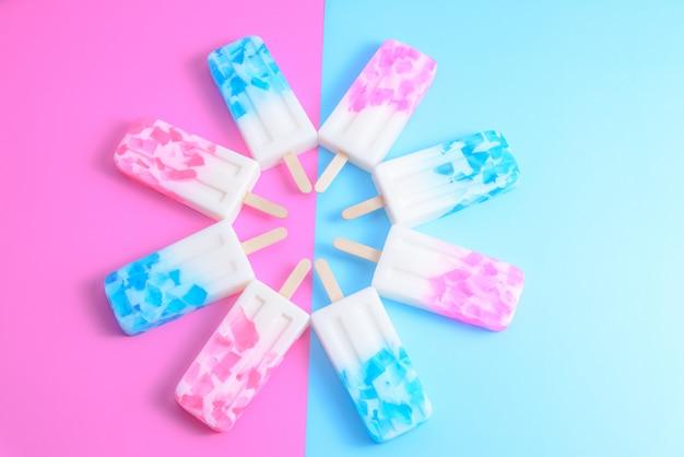 Bâtonnet de glace aux fruits, sucette glacée, boisson gazeuse ou boisson glacée avec fond sur fond de texture bleu et rose pastel