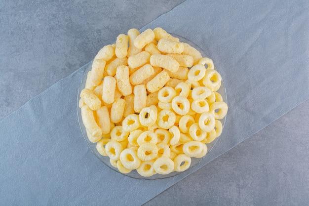 Bâtonnets et anneaux de maïs doux sur des morceaux de tissu, sur la surface de marbre