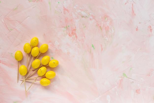 Bâtonnets en bois de pâques pour les amuse-gueules sur un rose
