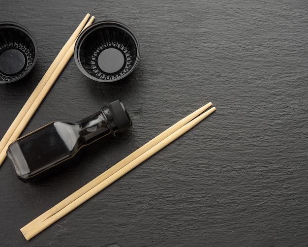 Bâtonnets en bois pour sushi, bouteille de sauce soja et assiettes en plastique jetables sur fond noir, ustensiles pour la livraison