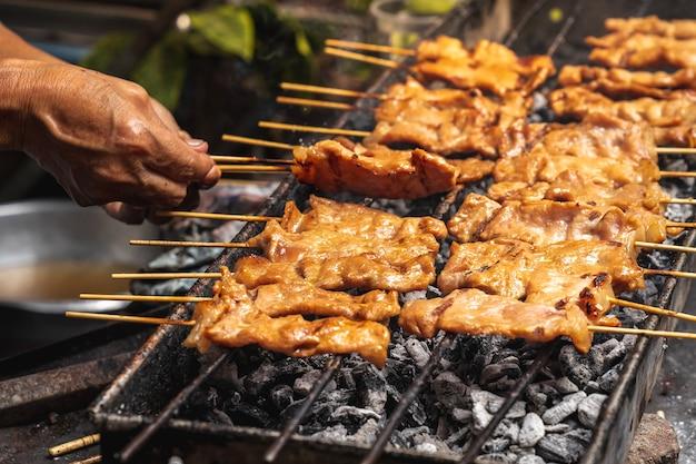Bâtonnets de brochette de porc grillé au charbon de bois grésillant sur le barbecue barbecue