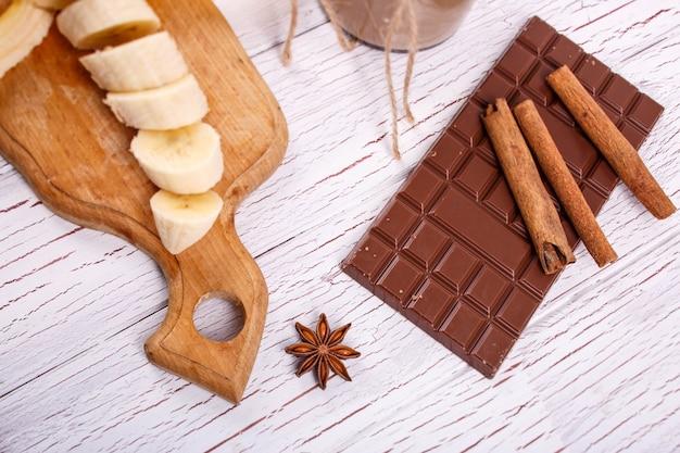 Les bâtonnets de cannelle reposent sur la barre de tranches de chocolat et de bananes