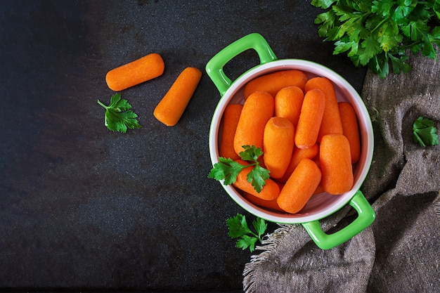 Bâtonnets de carotte bébé dans un bol vert sur une surface noire. concept d'alimentation saine. nourriture végétalienne. vue de dessus. mise à plat