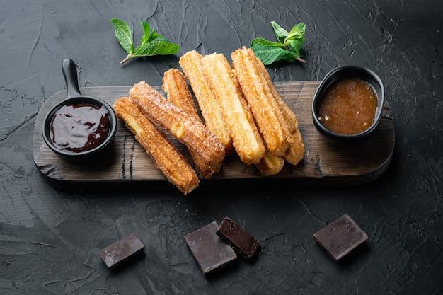 Bâtonnets de churros traditionnels avec cannelle et sucre en poudre, sur fond noir